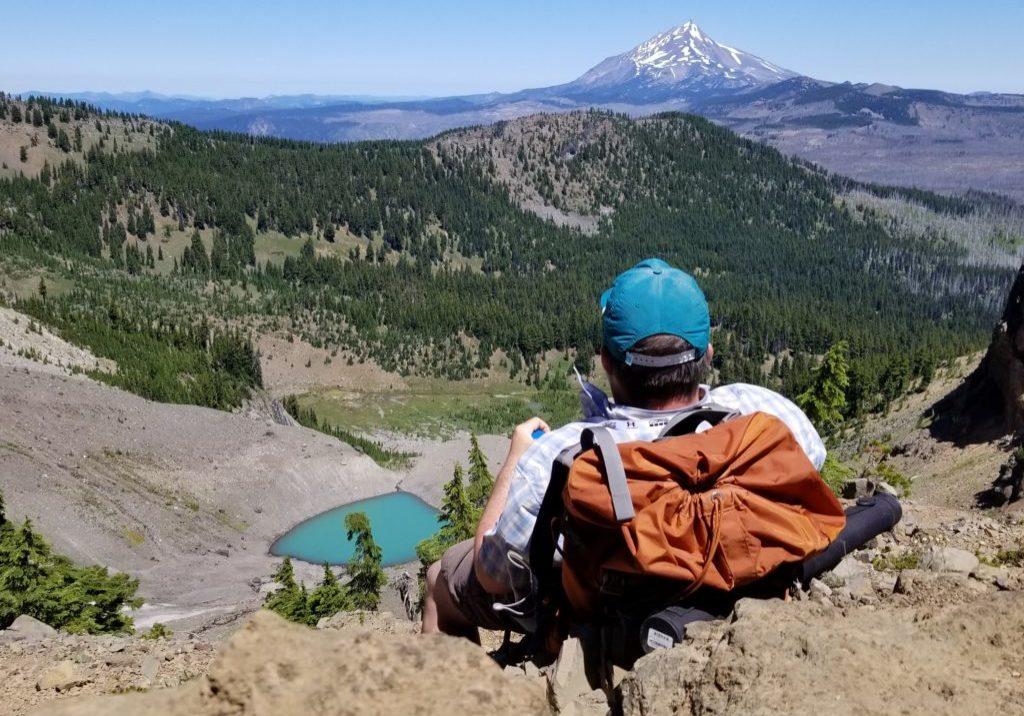 Backpacker looking across moraine landscape at Mt. Jefferson